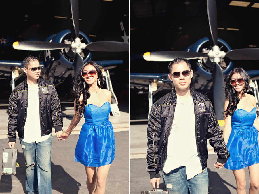 Couple in front of airplane hangar, vintage airplane