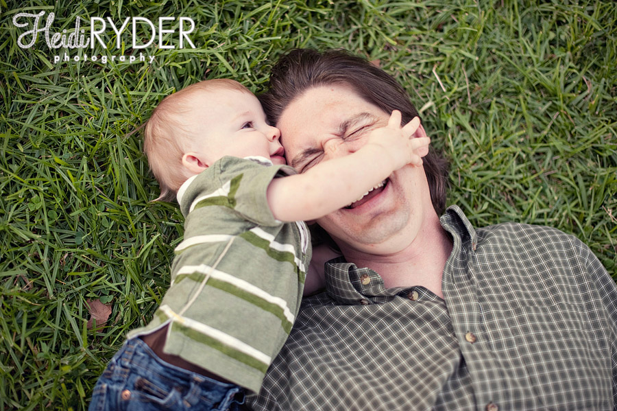 baby and dad lying in grass